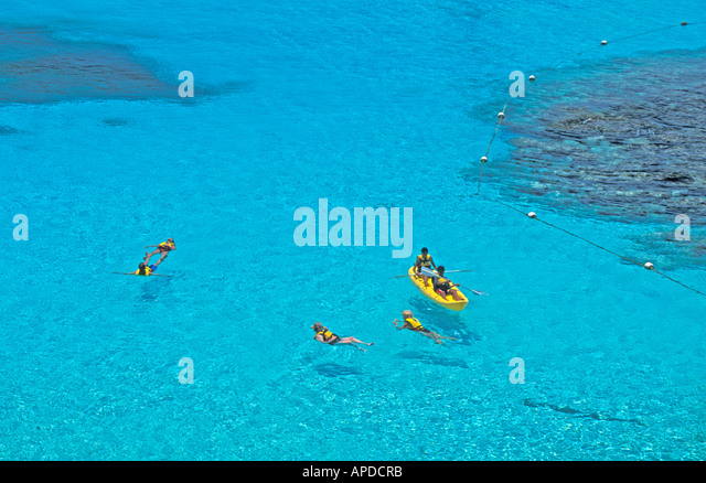Mexico Isla Mujeres Garrafon Natural Park kayak couple swimmers bright clear turquoise water - Stock Image