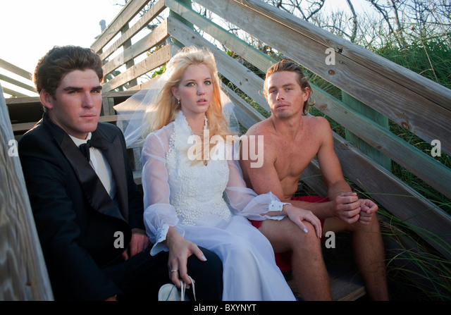 Young bride sitting at beach between groom and lifeguard - Stock Image