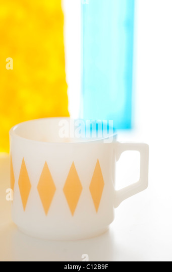coffee mug with blue and yellow and white patterns - Stock Image