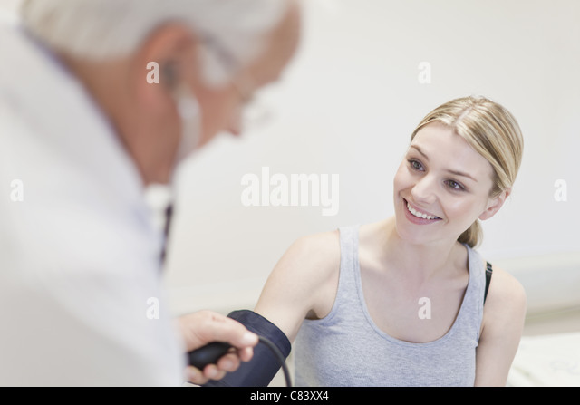 Doctor taking patient's blood pressure - Stock Image