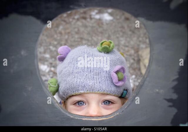 A young girl peeking through a hole. - Stock Image