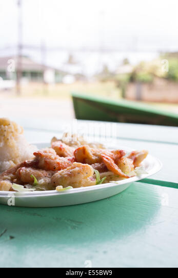 Plate of garlic shrimp and rice on turquouse table with street view in the background in North Shore, Hawaii. - Stock Image