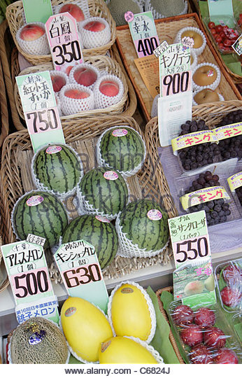 Tokyo Japan Ryogoku kanji hiragana katakana characters symbols fresh fruit display for sale melon peaches grapes - Stock Image