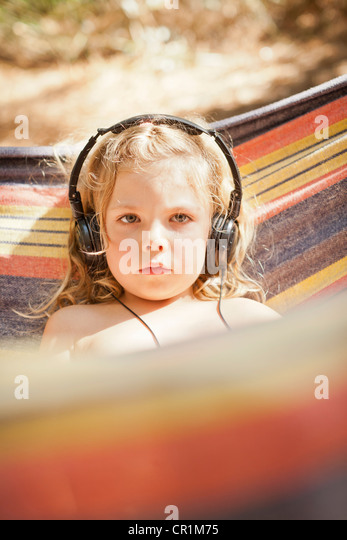 Girl listening to headphones outdoors - Stock Image