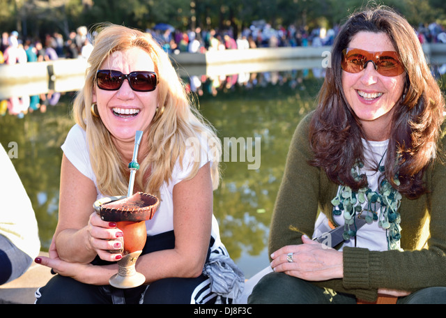 Brazil, Porto Alegre: 'Gaúchas' enjoying sunny winter day in the city park Farroupilha drinking 'Chimarrao' - Stock-Bilder
