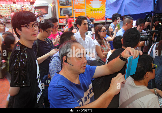 China Hong Kong Island Causeway Bay Yee Wo Street East Point Road Asian man smartphone camera taking picture - Stock Image