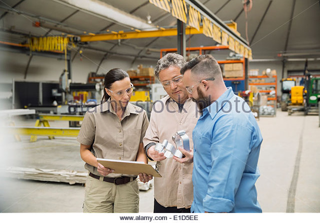 Workers examining metal parts in manufacturing plant - Stock Image