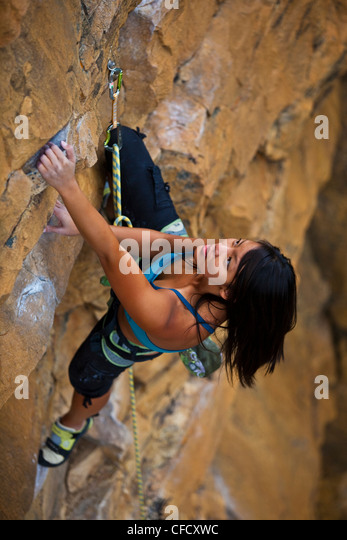 A young asian woman rockclimbing at Lost Boys crag in Jasper National Park, Alberta, Canada - Stock Image
