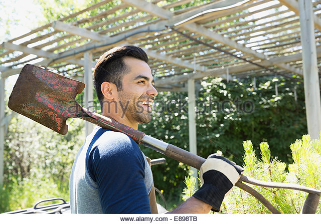 Smiling worker with shovel at plant nursery - Stock Image