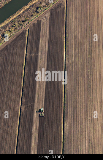 Aerial of a tractor plowing a farm field on John's Island, South Carolina. - Stock Image