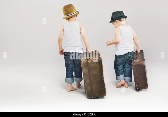 Two cute brothers leaving with their huge suitcases - Stock-Bilder