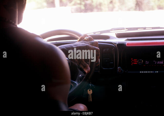 Cropped close up of young man driving on car road trip - Stock Image