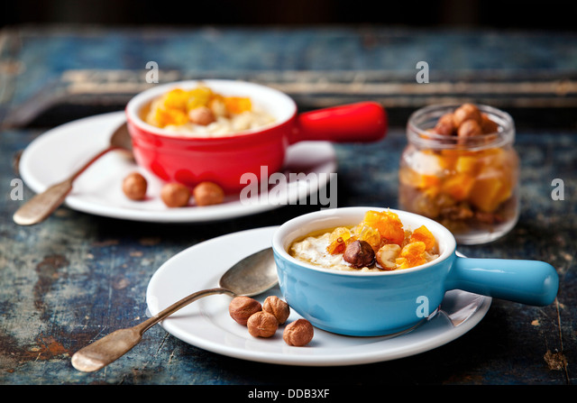 Oatmeal porridge with nuts and dried fruits - Stock Image