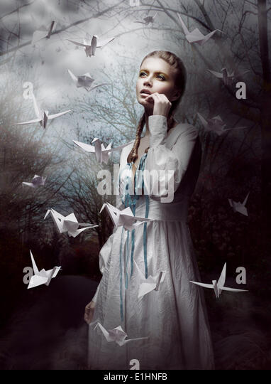 Night. Woman in  Mysterious Forest launching handmade paper Cranes. Origami - Stock Image