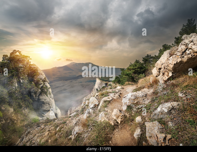 High rocks and gray clouds at sunset - Stock Image
