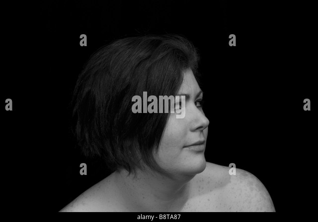 Dark haired woman with look of doubt on face - Stock Image