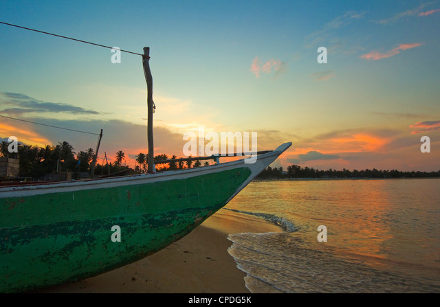 Outrigger boat at sunset at this fishing beach and popular tourist surf destination, Arugam Bay, Eastern Province, - Stock-Bilder