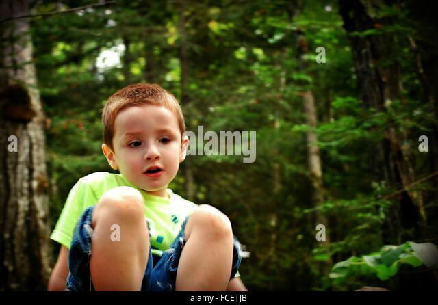 Cute Boy Sitting In Park - Stock Image