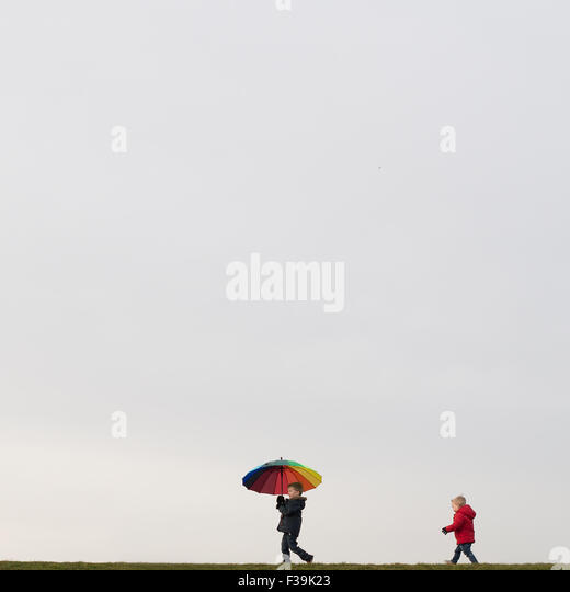 Boys walking, holding an umbrella - Stock Image