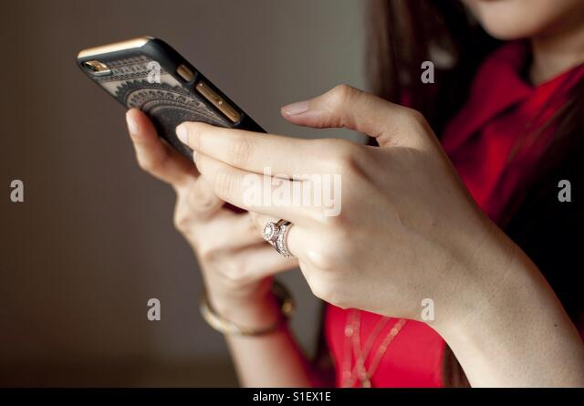 Hand of a woman with diamond ring and cellphone - Stock-Bilder