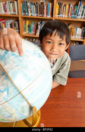 Student pointing to world globe - Stock-Bilder
