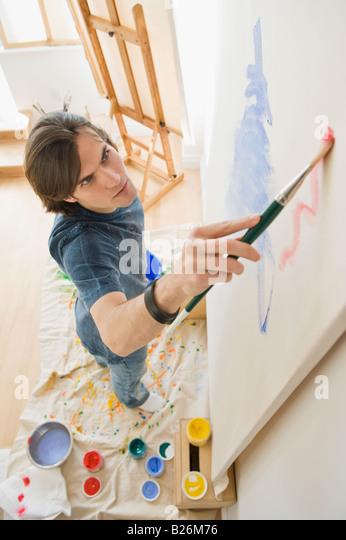 Man painting on easel - Stock-Bilder
