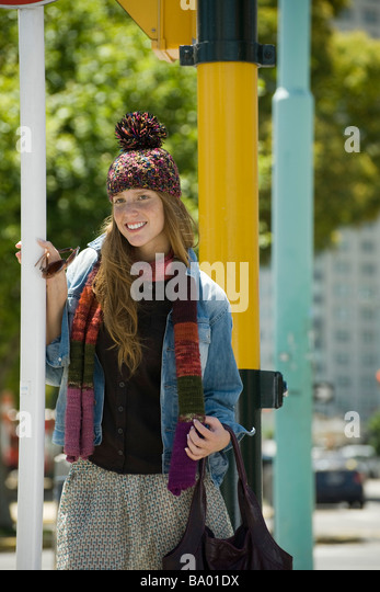 Young woman in trendy clothing, smiling - Stock Image