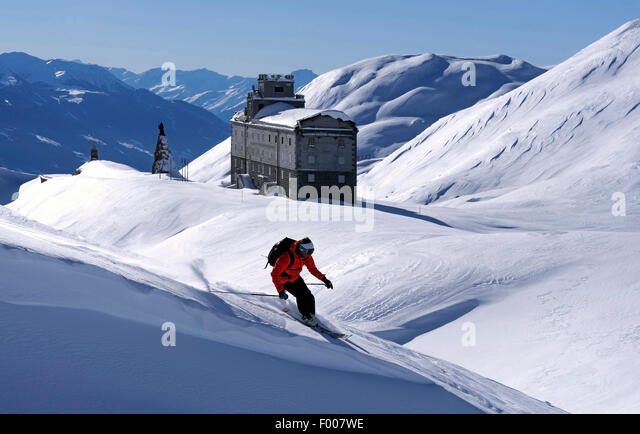 skiing in front of ancient hospice at Little St Bernard Pass, France, Savoie - Stock Image