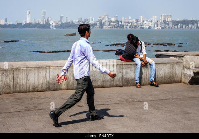 India Asian Mumbai Churchgate Marine Drive Back Bay Arabian Sea man woman couple romantic Malabar Hill skyline pedestrian - Stock Image