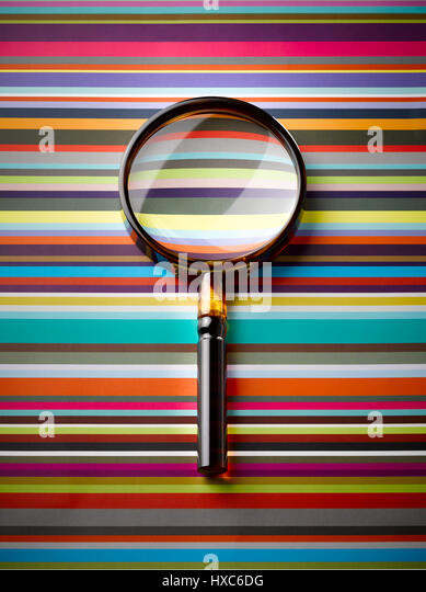 Magnifying glass on striped background - Stock Image