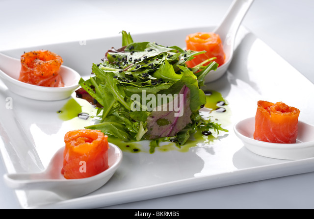 Salmon in a white plate. In the middle of rucola salad. - Stock Image