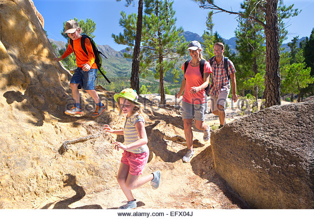 Family hiking on mountain path - Stock Image
