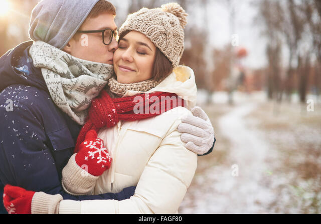Happy guy kissing his girlfriend outdoors - Stock Image