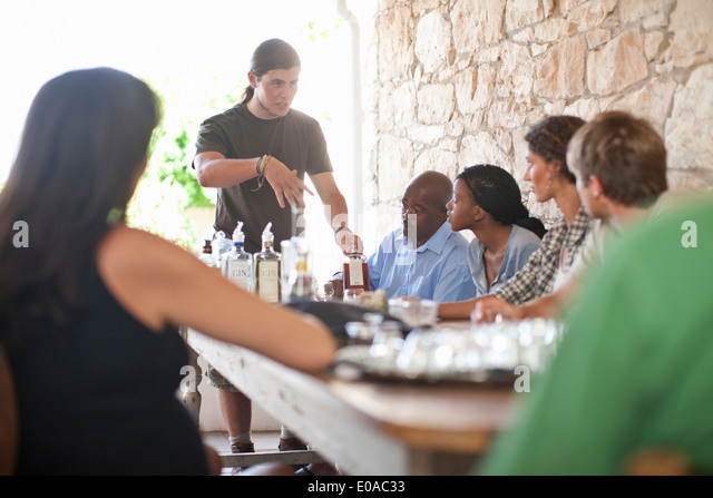 People sitting around table, tasting drinks - Stock Image
