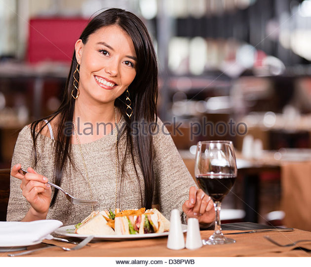 Woman at a restaurant having lunch and looking happy - Stock Image