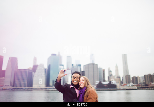 Young couple taking selfie with Manhattan skyline, New York, USA - Stock Image