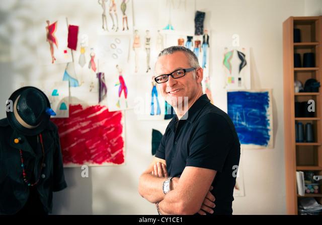 Confident entrepreneur, portrait of happy mature man working as fashion designer and dressmaker in atelier - Stock-Bilder