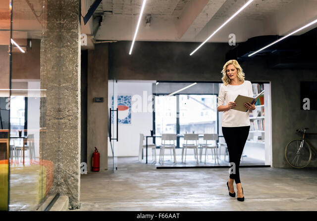 Attractive businesswoman in office holding notebook - Stock Image