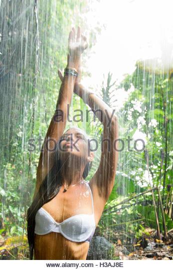 young Tahitian woman enjoying the rain - Stock Image