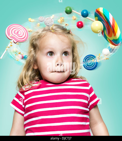 Little girl with flying candies around her head, Composite - Stock Image