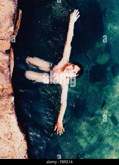 High Angle View Of Shirtless Boy Swimming In Sea - Stock Image