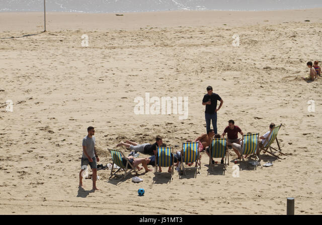 Bournemouth, UK -  13 May: People seen basking in the sun on the sandy Bournemuth beach. General view of the seaside - Stock Image