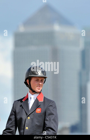 Ben Mayer (GBR) looks at the fences with Canary Wharf in the background. Show Jumping Demonstration Competition. - Stock Image