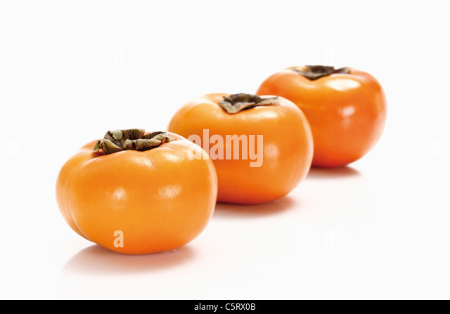 Kaki fruits in a row - Stock Image