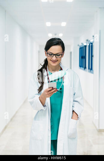 Beautiful doctor writting on cellphone at hospital. - Stock Image