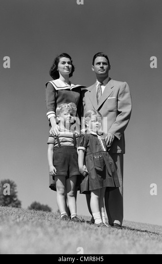 1950s FAMILY PORTRAIT FATHER MOTHER DAUGHTER SON STANDING TOGETHER OUTDOOR - Stock Image