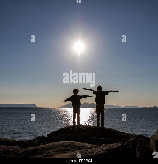 Two boys (6-7) pretending to fly - Stock Image