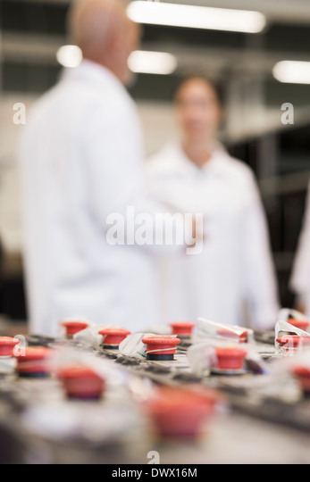 Selective focus on machine parts with engineers in background at industry - Stock Image