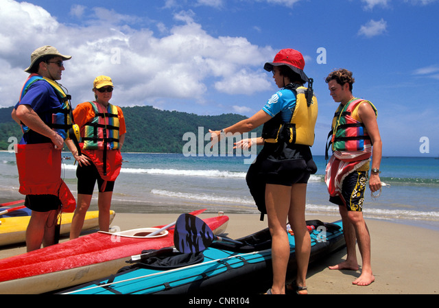 Kayakers preparing to launch kayaks from beach in the Caribbean on the island of Trinidad. - Stock Image