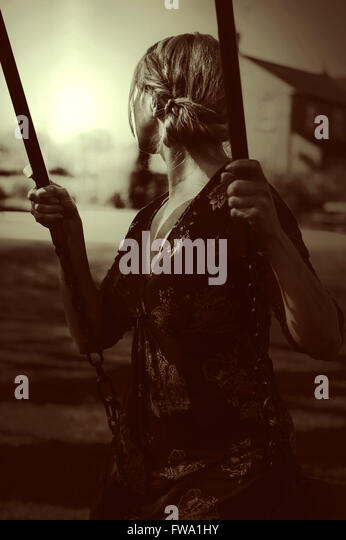 young woman sitting on the swing - Stock-Bilder